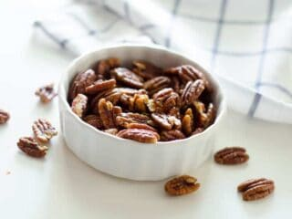 small bowl of pecans with dish towel in background