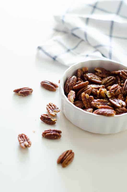 Bowl of pecans with white and blue dishtowel in the background and pecans scattered nearby