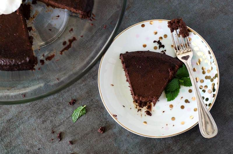 overhead view of a slice of paleo flourless chocolate cake on a plate with a fork taken from a nearby cake