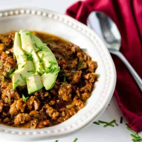white bowl full of chili topped with avocado slices with red napkin and spoon next to it