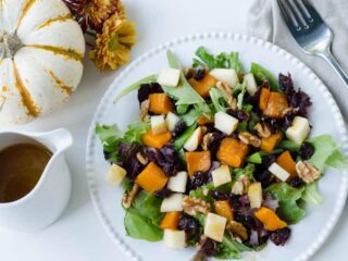 overhead view of plated fall salad with salad dressing and a decorative pumpkin in the background