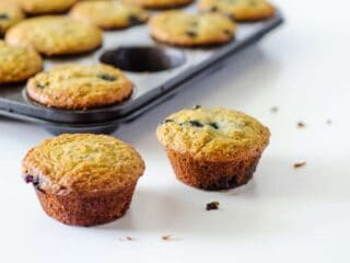 2 muffins on table with pan in background