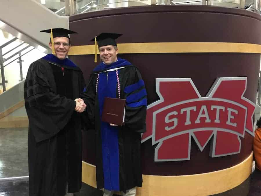 Two men shaking hands at MSU graduation ceremony