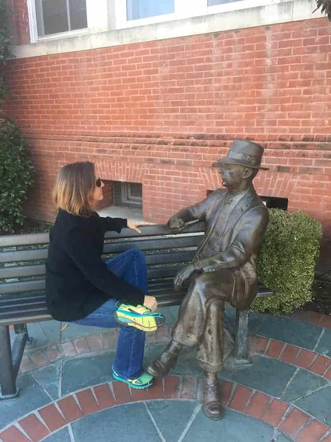 Woman sitting on bench with William Faulkner statue