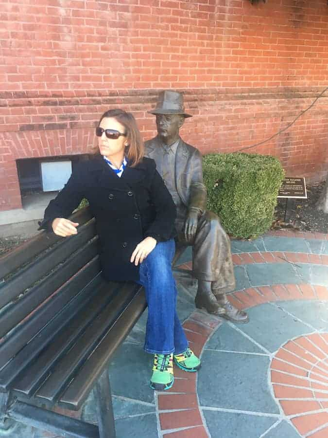 Woman sitting on bench with William Faulkner statue, mimicking his pose