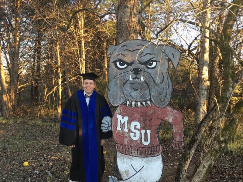 Man in graduation gown standing with MSU bulldog cutout in woods