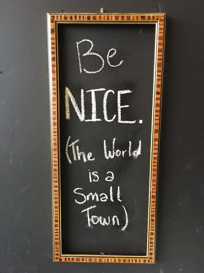 """sign reading """"Be Nice. The world is a small town."""""""