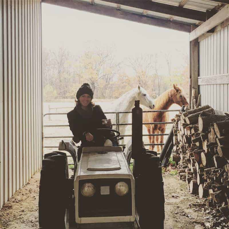 Woman on tractor with horses in background
