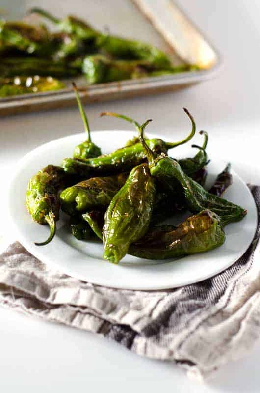 Side view of roasted shishito peppers on a plate with pan in the background