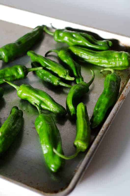 Roasting pan with raw bright green shishito peppers on it