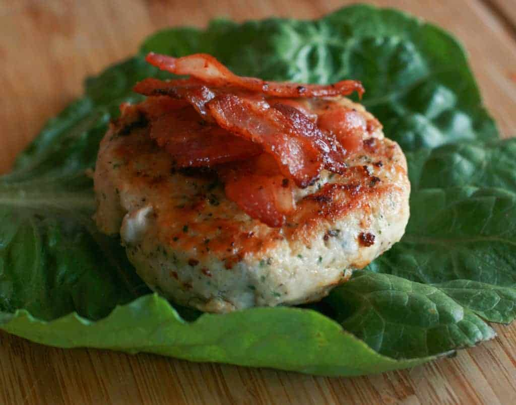 side view of a chicken burger topped with bacon on a lettuce leaf