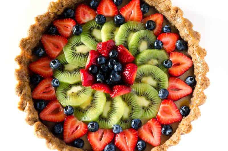 Overhead view of a paleo fruit tart topped with berries and kiwi
