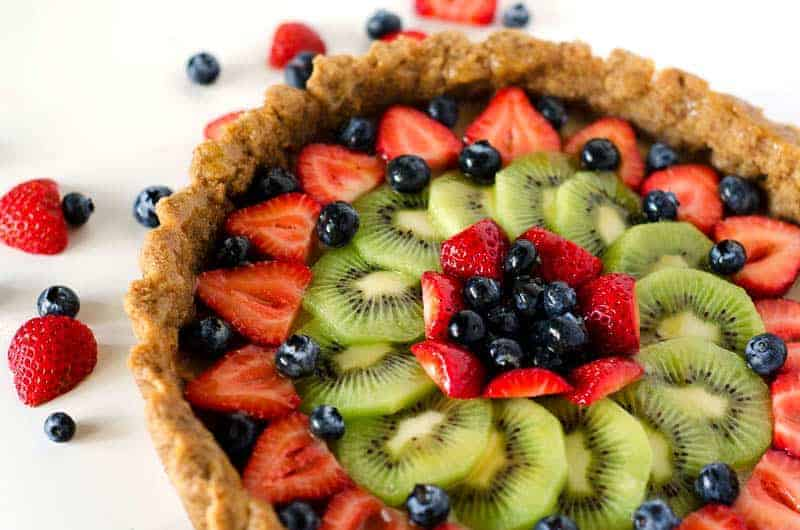 Side view of a mixed fruit tart surrounded by berries