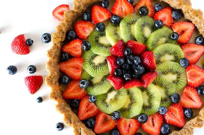 Overhead view of a paleo mixed fruit tart surrounded by berries