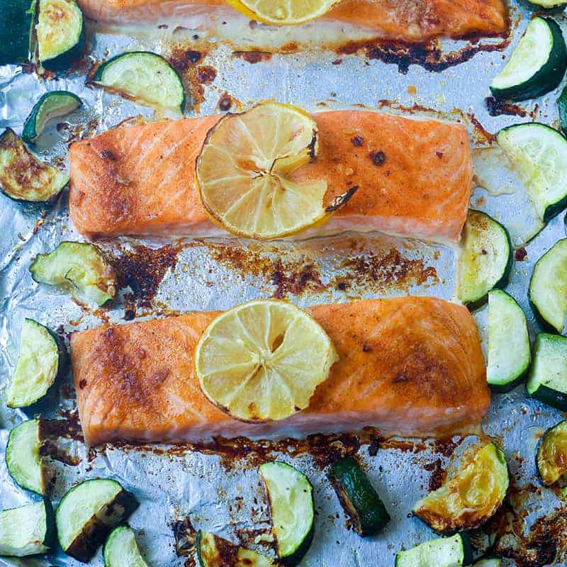 overhead view of salmon filets topped with lemon on a foil lined pan