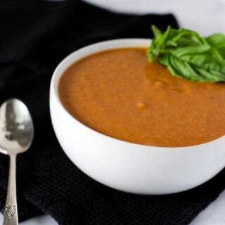 side view of a bowl of tomato basil soup garnished with basil leaves