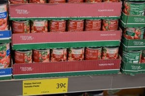 cans of tomato paste on shelf at Aldi
