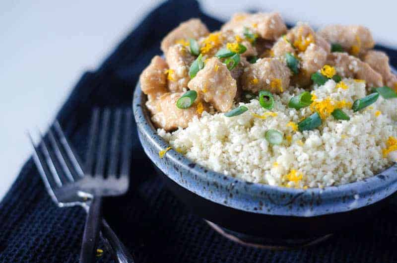 side view of a bowl of sesame orange chicken and cauliflower rice topped with green onions and orange zest