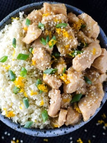 overhead view of a bowl of sesame orange chicken with cauliflower rice