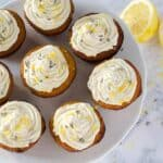 Overhead view of lemon lavender cupcakes on a cake stand with a lemon in the background