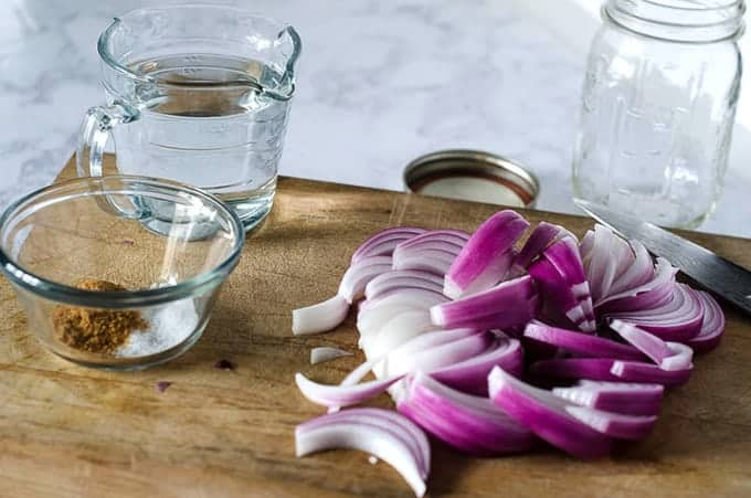 Side view of a cutting board with sliced red onion and pickling ingredients