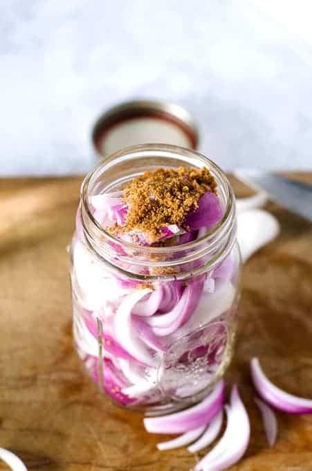 Overhead view of the top of a mason jar packed with red onion slices sprinkled with sugar and salt