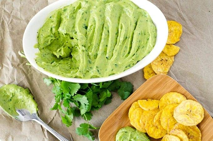 Overhead view of bowl of avocado dip surrounded by spoon, loose cilantro, and plate of chips