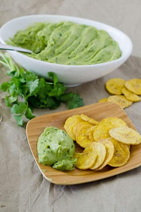 Side angle view of bowl of avocado dip with plate of chips