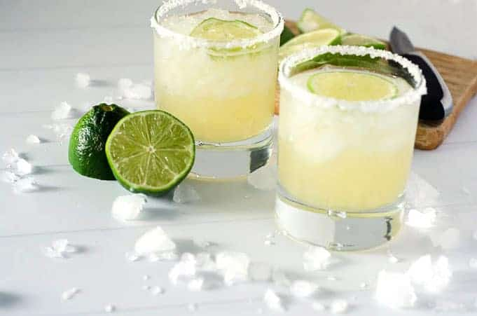 side angle view of two salt-rimmed margaritas in glasses surrounded by limes and ice