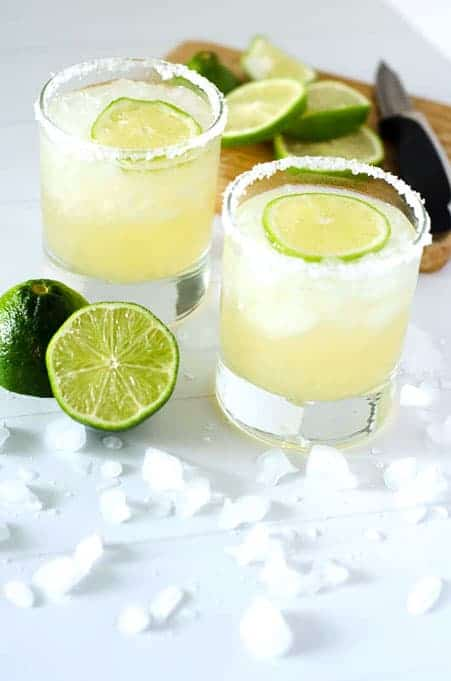 two glasses of margaritas on the rocks surrounded by limes and ice