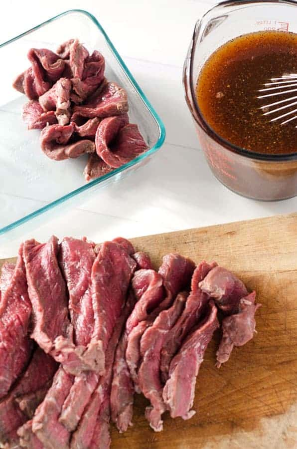overhead view of raw meat on cutting board and in a pan with marinade next to it