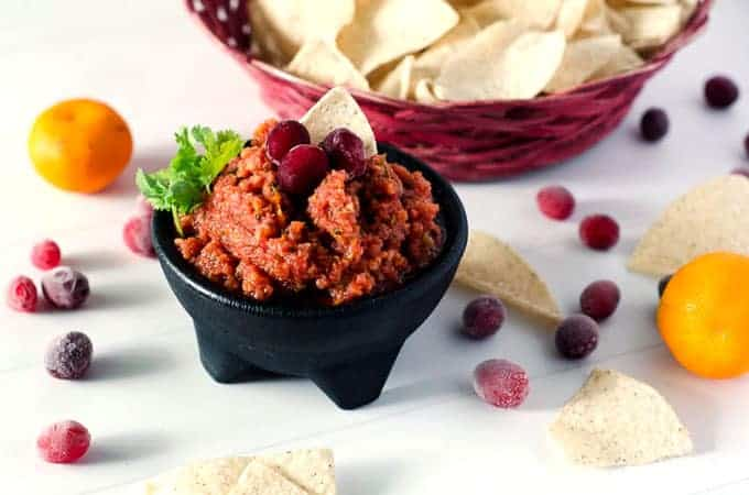side view of black bowl full of cranberry orange salsa with a basket of chips in the background