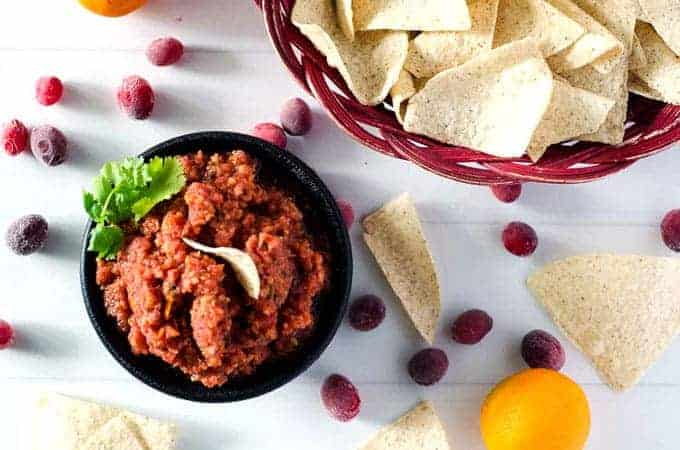 overhead view of a bowl of cranberry orange salsa and a basket of chips surrounded by cranberries and chips