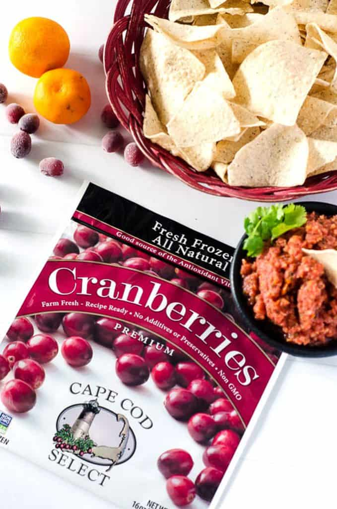 overhead view of a bowl of cranberry orange salsa, a basket of chips, and frozen cranberry package