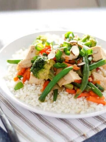 plate of paleo chicken stir fry on top of a striped napkin with a fork and glass of water