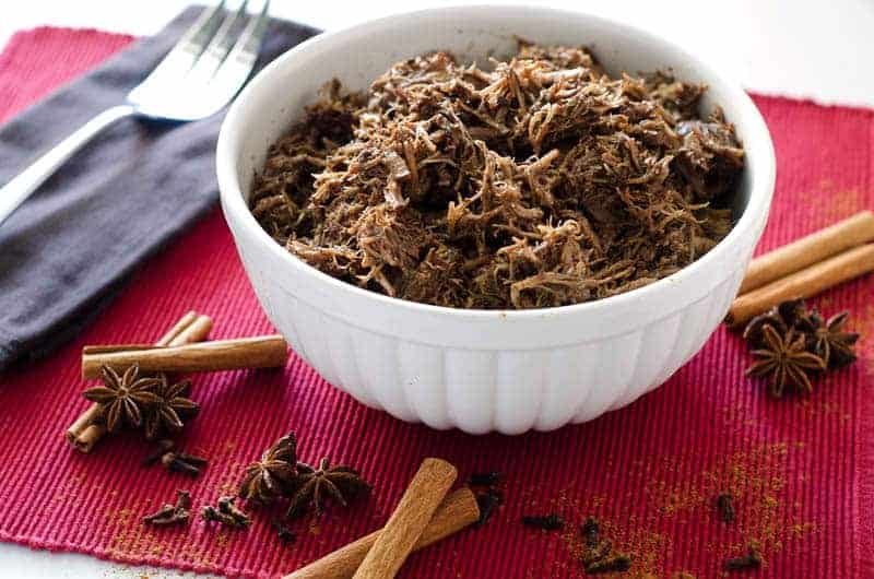 white bowl of pulled pork surrounded by whole spices on a red placemat