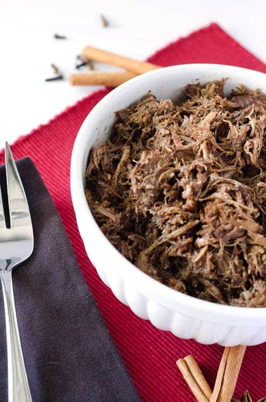 white bowl of pulled pork on a red placemat with large silver serving fork