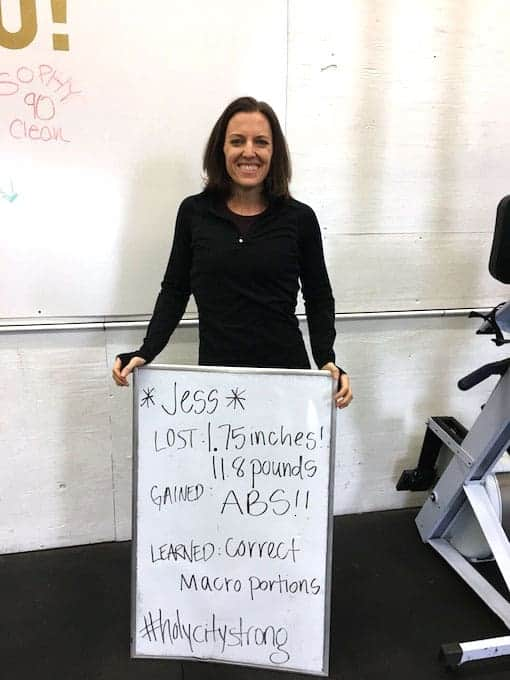 Woman holding whiteboard showing weight loss results from eating paleo macros