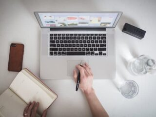 overhead view of person working with laptop, notebook, and pen