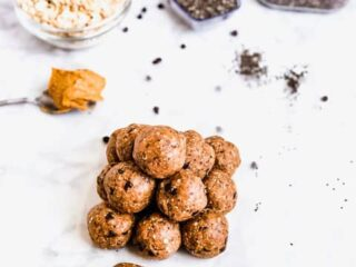 Pile of energy ball snacks on counter surrounded by oats, peanut butter and chia seeds