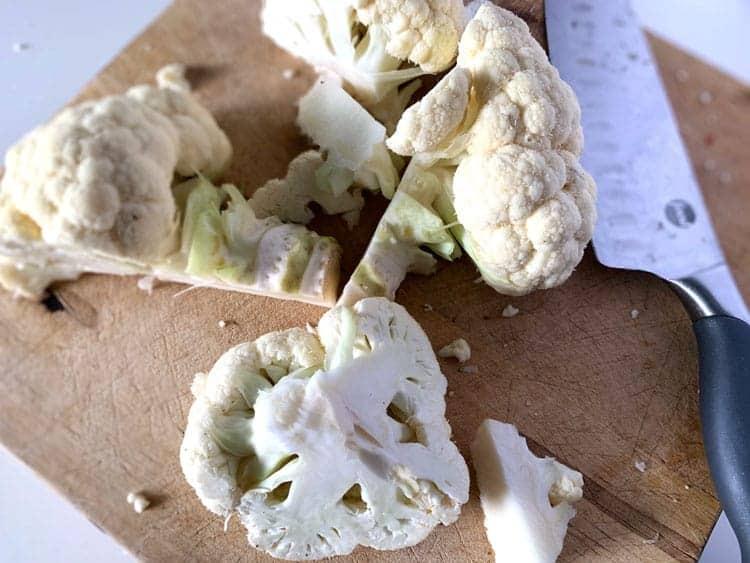 head of cauliflower cut up on cutting board