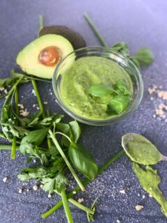 bowl of green goddess salad dressing surrounded by herbs and ingredients