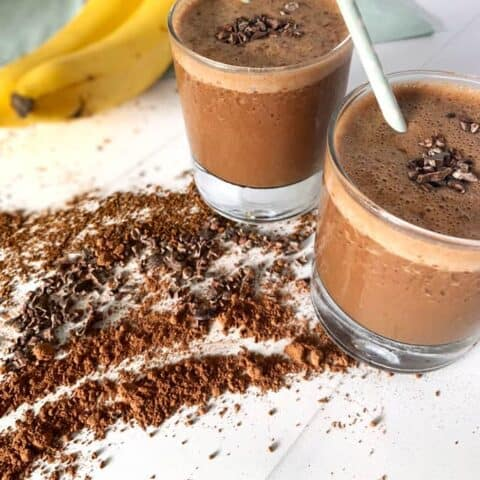 two banana coffee smoothies on countertop surrounded by cocoa powder, coffee, and bananas