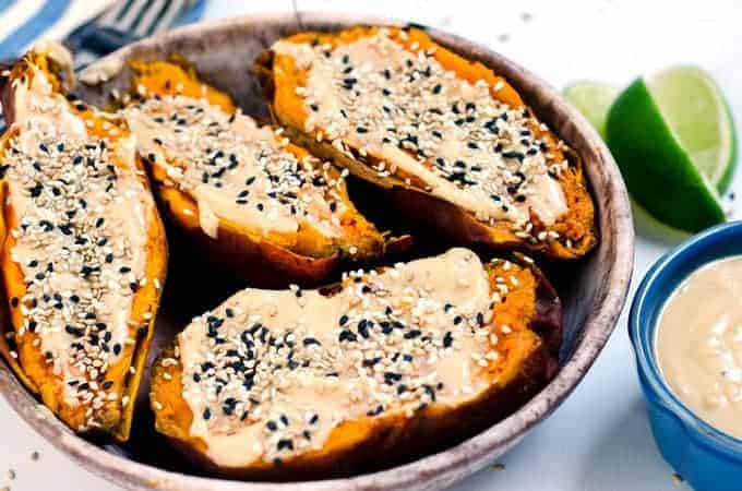 bowl of halved sweet potatoes topped with tahini spread and sesame seeds