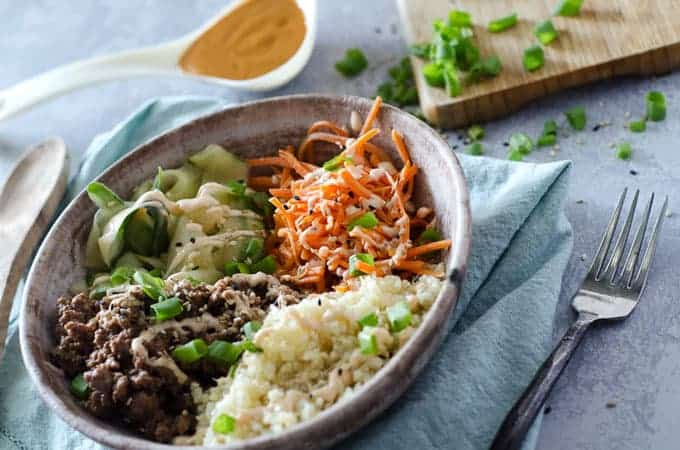View of table with korean ground beef bulgogi bowl surrounded by kitchen tools and ingredients
