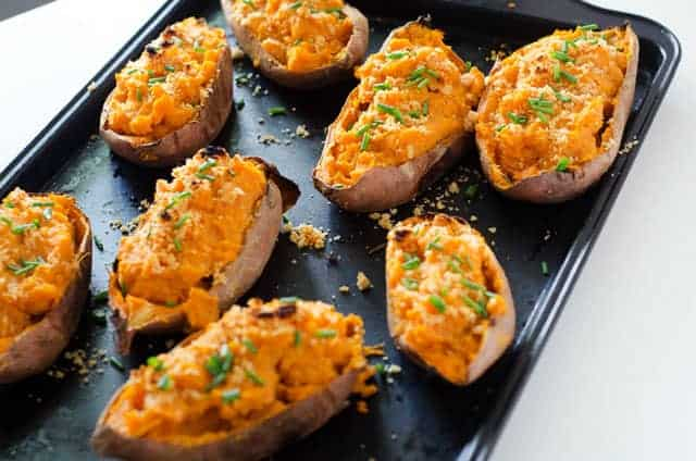 baking sheet with baked sweet potatoes cut in half