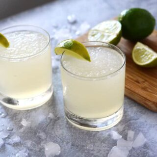 two glasses of frozen limeade surrounded by ice and a cutting board with limes