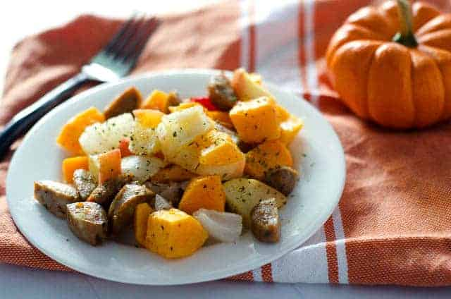 plate of sausage and vegetables on top of an orange napkin with a pumpkin in the background