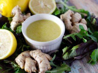 bowl of ginger dressing surrounded by lettuce, ginger, and lemons
