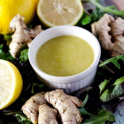 bowl of ginger dressing surrounded by lemons, ginger, and lettuce leaves